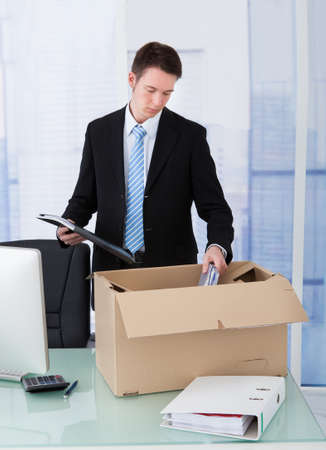 Young businessman collecting office supply in cardboard box at office desk photo