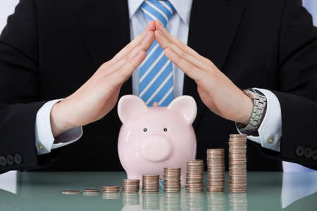 sheltering: Midsection of young businessman sheltering piggybank and coin stacks at office desk