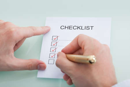 Cropped image of businessman preparing checklist at office desk photo