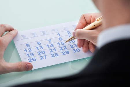mans: Closeup of mans hand marking date 15 on calendar Stock Photo