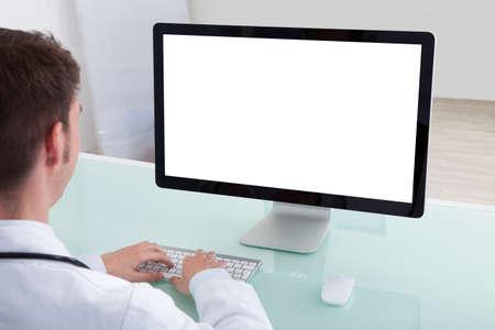 monitor de computadora: Retrato del doctor de sexo masculino joven confidente que trabaja en el ordenador en el escritorio en el hospital
