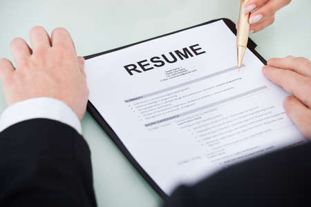 Cropped image of young businessman with resume at desk photo