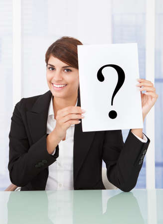 obscured face: Businesswoman holding paper with question mark in front of face at desk in office