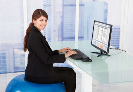 Side view of businesswoman using computer while sitting on fitness ball at desk in office photo