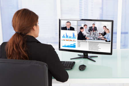 conferencing: Rear view of businesswoman video conferencing with team on computer at desk in office Stock Photo