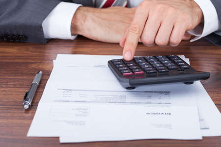 calculation: Midsection of businessman using calculator on invoice documents at office desk