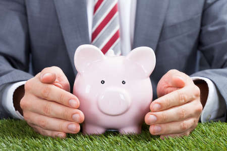sheltering: Midsection of businessman sheltering piggybank on grass