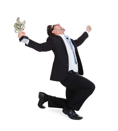 Full length of successful young businessman with trophy screaming over white background photo