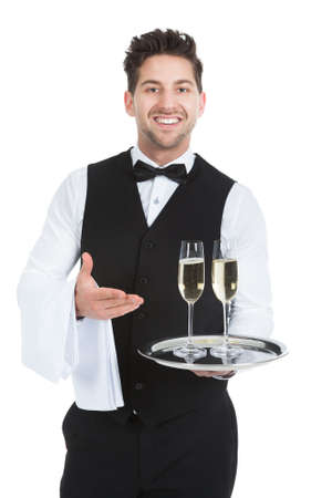 alcohol server: Portrait of confident waiter carrying champagne flutes on tray over white background