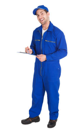 Young male mechanic in overall writing on clipboard over white background photo