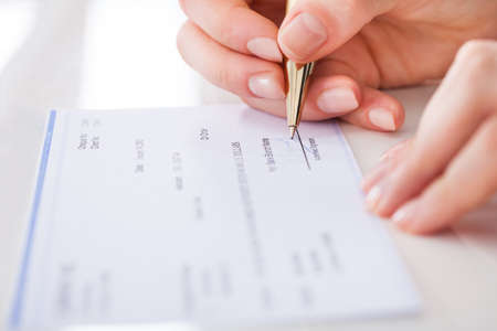 background check: Cropped image of businesswoman signing cheque at desk
