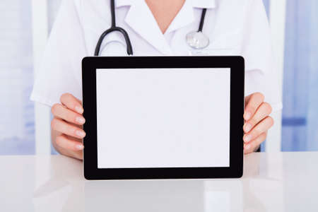 midsection: Midsection of female doctor displaying digital tablet at desk in hospital Stock Photo