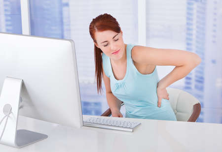Young businesswoman suffering from backache at computer desk in office photo