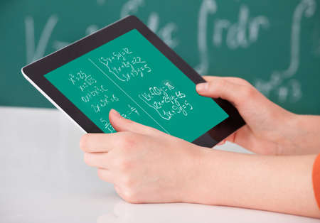 Cropped image of young female student solving maths problem on digital tablet in classroom