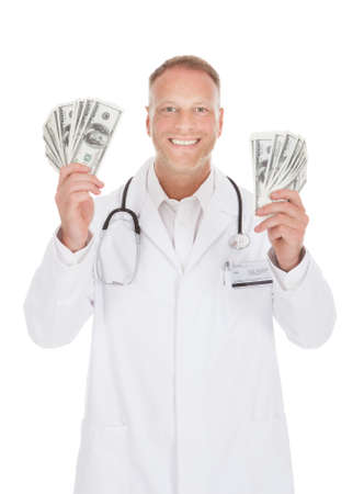 Portrait of smiling male doctor holding banknotes over white background photo