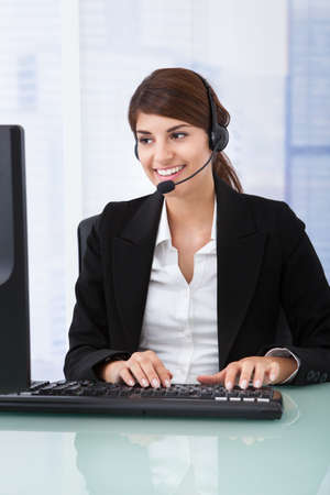 telephone headsets: Portrait of confident young businesswoman wearing headset at computer desk