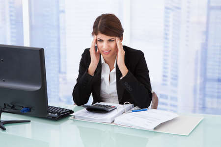 Stressed young businesswoman suffering from headache at computer desk in office photo