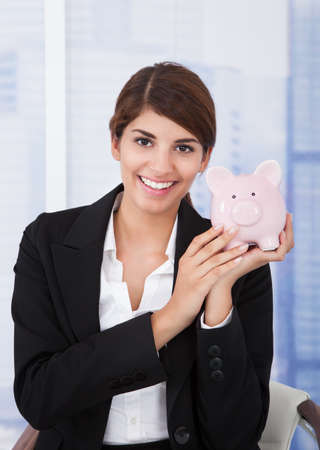 coinbank: Portrait of happy young businesswoman holding piggybank in office Stock Photo
