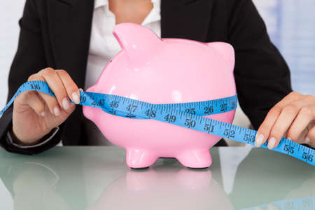 woman measuring: Midsection of businesswoman measuring piggybank with measure tape at desk