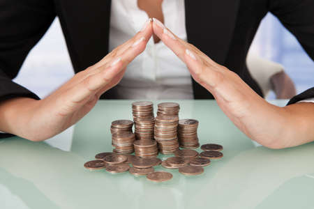 Midsection of businesswoman sheltering coins in house shape on desk photo