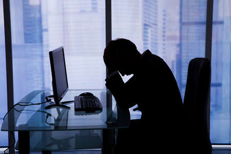 Side view of tired young businessman sleeping at computer desk in office photo