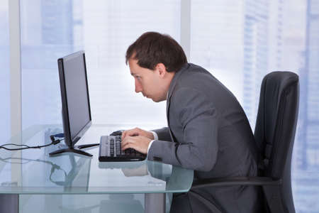 side views: Side view of concentrated businessman working on computer at desk in office Stock Photo