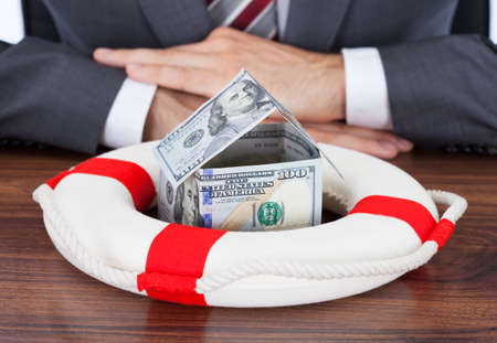 Midsection of businessman protecting money house with lifebuoy on table photo