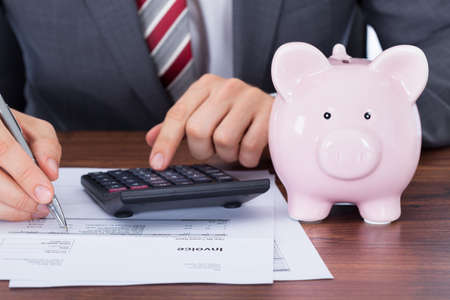 midsection: Midsection of businessman calculating invoice by piggybank and coins on desk Stock Photo