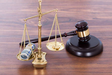 Judge gavel and scales with money on wooden desk