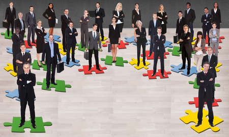 Group of multi ethnic business people standing on jigsaw pieces photo