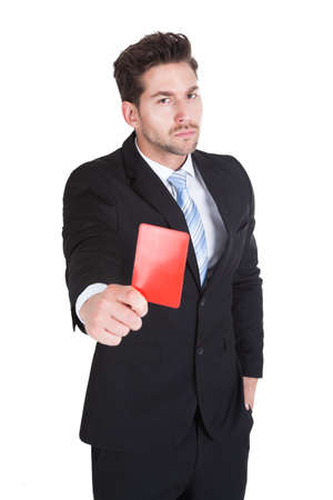 Portrait of handsome young businessman showing red card over white background photo