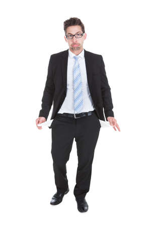unsuccessful: Full length of young businessman showing empty pockets over white background