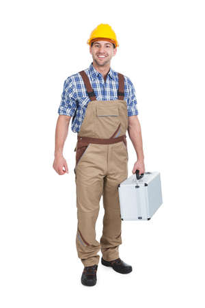 Full length portrait of young manual worker with toolbox over white background photo