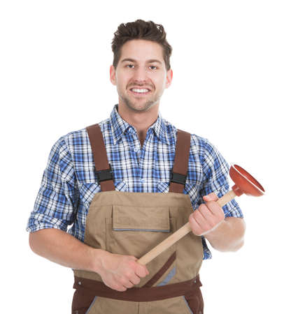 Full length portrait of excited young male plumber holding plunger over white background photo