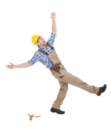 Full length of young manual worker falling over white background photo