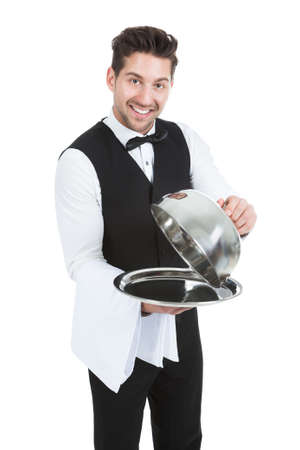 cloche: Portrait of butler lifting cloche from serving tray over white background