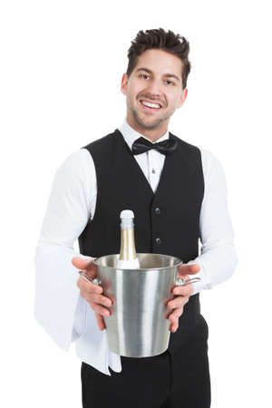 Portrait of confident young waiter holding ice bucket with champagne bottle over white background photo