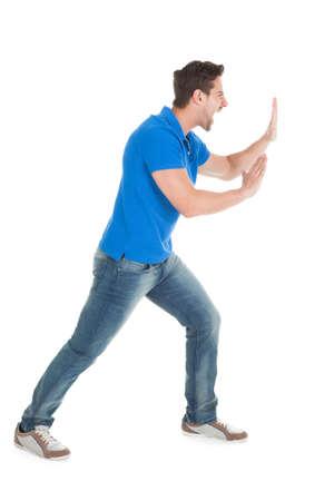 Full length portret van vertrouwen man duwen billboard op een witte achtergrond Stockfoto