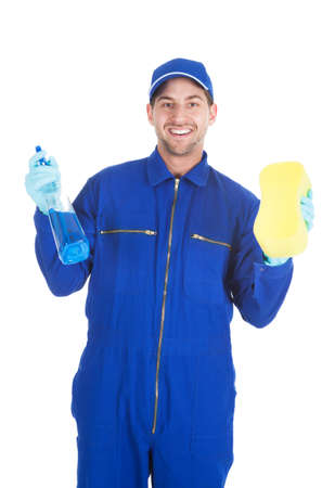 Portrait of confident young servant holding cleaning spray and sponge over white background photo