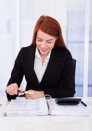 Smiling young businesswoman examining documents with magnifying glass at office desk photo