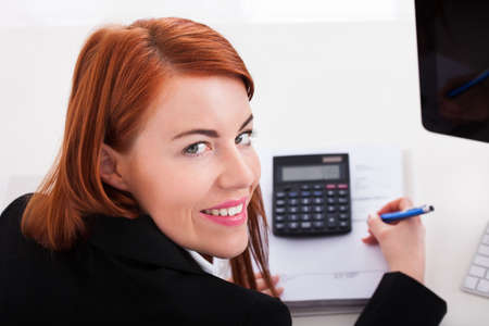 Cropped image of businesswoman using calculator while working at office desk photo