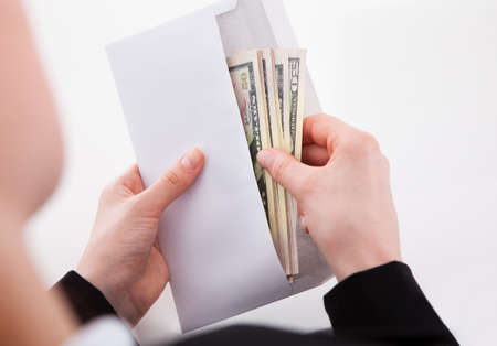 Cropped image of businesswoman putting American banknotes in envelope at office photo