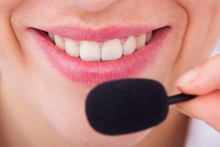Closeup of smiling female customer service representative with microphone photo