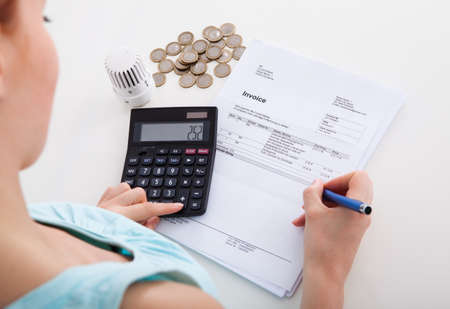 High angle view of young woman calculating invoice by coins and thermostat at desk