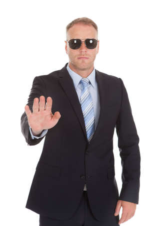 seguridad en el trabajo: Retrato de guardaespaldas confiado haciendo parada gesto m�s de fondo blanco