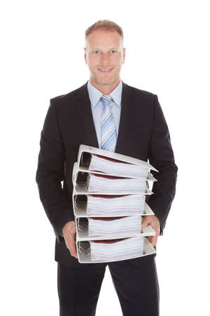 Portrait of happy mid adult businessman carrying stack of binders over white background photo