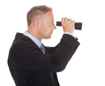 Portrait of confident mid adult businessman looking through binoculars over white background photo