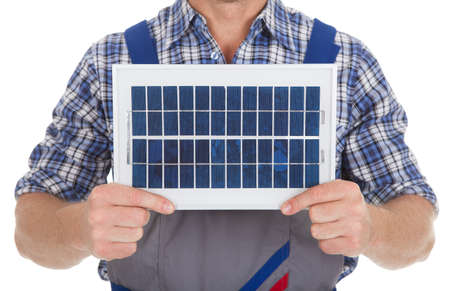 Midsection of manual worker holding solar panel over white background photo