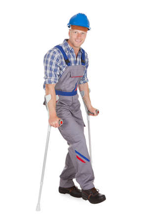 Full length portrait of handyman walking with crutches over white background photo