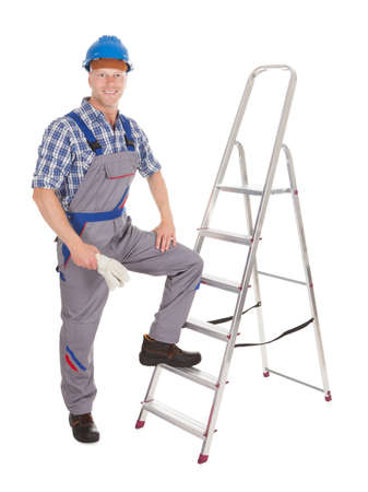 Portrait of confident repairman with ladder over white background photo